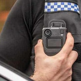 An image displaying a Motorola Solutions VB400 body-worn camera donned on the chest area of a Policeman's uniform Vest