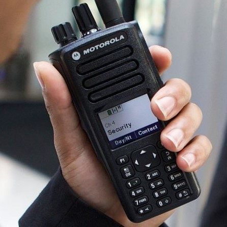 An image displaying the Motorola Solutions MOTOTRBO DP4800 DMR Radio device being used by a hotel worker wearing a suit