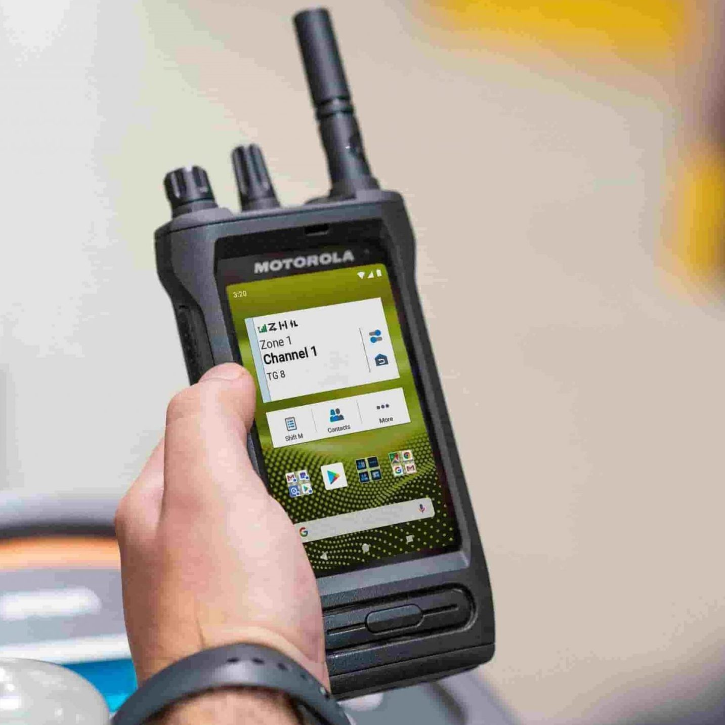 An image displaying the Motorola Solutions MOTOTRBO Ion Smart Radio device being used by a worker driving a forklift in a warehouse storage location